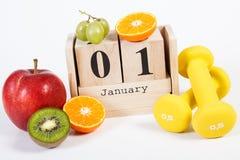 Cube o calendário, os frutos e os pesos, anos novos das definições, estilo de vida saudável Fotografia de Stock Royalty Free