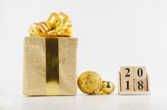 Cube o calendário pelo ano novo 2018 com caixa de presente e as decorações douradas no fundo branco Foto de Stock Royalty Free