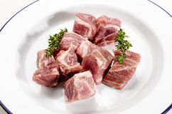 Cube pork neck with thyme on a blue and white plate Stock Photo