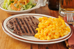 Cube steak dinner. Grilled cube steak with macaroni and cheese and a mug of beer stock photography