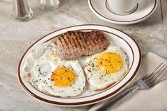 Cube steak and eggs for breakfast. High angle view of a plate of steak and eggs served for breakfast stock images