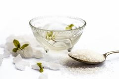 Close up of sugar syrup in a glass bowl along with sugar cubes and some mentha or mint leaves. Cube sugar or crystallized sugar with its syrup and mint leaves stock images