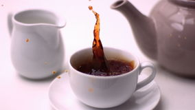 Cube of sugar falling in tea cup. In slow motion stock footage