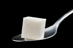 Cube of sugar on spoon. Isolated on black background Stock Photo