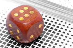 Cube to play. Brown lacquered wooden dice with the number six with a background of playing cards Stock Images