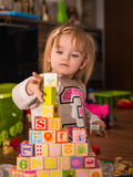 Cube toys. Baby girl 1,5 years old playing on a floor in living room Royalty Free Stock Photo