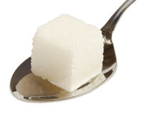 Cube of white sugar on spoon Royalty Free Stock Images
