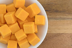 Cubed mild cheddar cheese in a white bowl Stock Photos