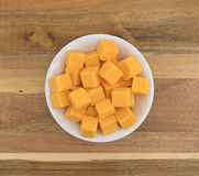 Cubed mild cheddar cheese in a white bowl Stock Image
