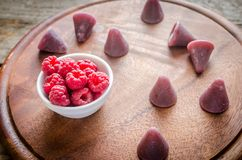 Cuberdons with fresh raspberries on the wooden board Stock Photo