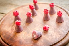 Cuberdons with fresh raspberries on the wooden board Royalty Free Stock Image