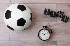 Cubes avec le réveil et le ballon de football image stock