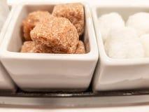 Cubes blancs et en sucre roux dans un sucrier de porcelaine images stock