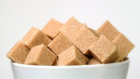 Cubes of brown cane sugar in bowl rotating close-up on white stock footage