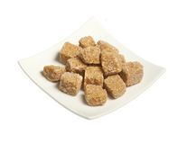 Cubes of  brown cane sugar in plate, isolated. Cubes of  whole cane sugar in plate, top view, isolated on the white background Royalty Free Stock Photos