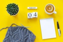 Cubes calendrier 4 février en bois Tasse de thé avec le citron, bloc-notes ouvert vide pour le texte Pot avec le tissu succulent  photos stock