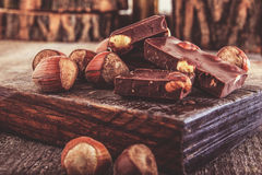 Cubes of chocolate with hazelnuts or nuts around Stock Photo