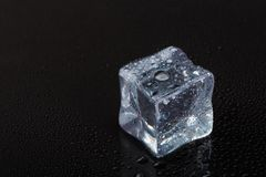 Cubes of clear ice on a black table royalty free stock image