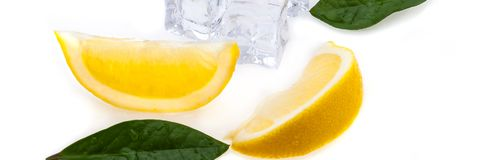 Cubes of cold ice, two slices of fresh lemon and green leaves on white isolated background. royalty free stock photo