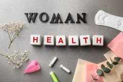 Cubes composed words WOMAN and HEALTH on grey table royalty free stock image