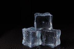 Cubes de glace claire sur une table noire images stock