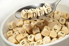 Cubes dice with with spoon alphabet soup with the german words for good idea - gute idee. Cubes dice with with alphabet soup spoon with the german words for good stock image