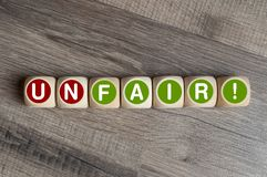 Cubes and dice with fair and unfair on wooden background royalty free stock photography