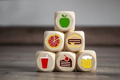Cubes and dice with fast food smybols and on top an apple for diet royalty free illustration