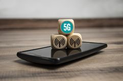 Cubes dice with 5G internet broadband standard. On wooden background stock image