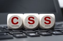 Cubes and dice on laptop keyboard with CSS cascading style sheets stock photo
