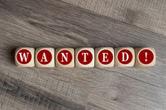 Cubes and dice with word wanted on wooden background stock photo