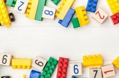 Cubes en bois avec des nombres et des briques colorées de jouet Photographie stock libre de droits