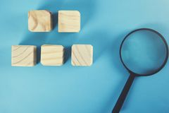 Cubes en bois avec la loupe photos stock