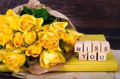Cubes en bois avec la MLLE YOU et bouquet d'inscription des fleurs jaunes sur le papier de vintage, fond en bois sélecteur Photographie stock libre de droits