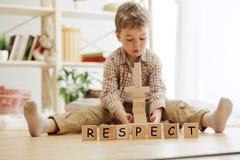 Cubes en bois avec le mot RESPECT dans des mains de peu de garçon photographie stock libre de droits