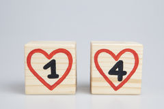 Cubes en bois avec les coeurs manuscrits de rouge d'intérieur du numéro un et quatre Photographie stock libre de droits