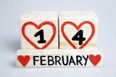 Cubes en bois avec les un et quatre coeurs rouges manuscrits d'intérieur, février Photographie stock libre de droits