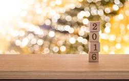 Cubes en bois avec 2016 sur la table au-dessus du fond de bokeh de tache floue, nouveau Images stock