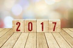 Cubes en bois avec 2017 sur le bois de perspective au-dessus du backg de bokeh de tache floue Photos stock