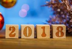 Cubes en bois 2018 Cometh la nouvelle année Fond brouillé un endroit pour un label Avec la nouvelle année photo libre de droits