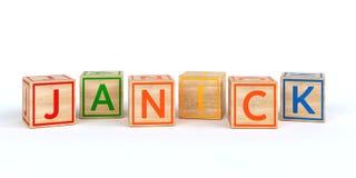 Cubes en bois d'isolement en jouet avec des lettres avec le janick de nom Photo stock