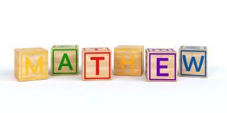 Cubes en bois d'isolement en jouet avec des lettres avec le mathew de nom Image stock