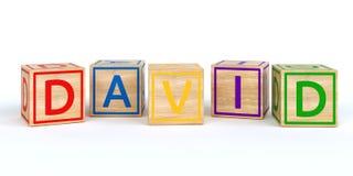 Cubes en bois d'isolement en jouet avec des lettres avec le nom David Photo stock