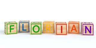 Cubes en bois d'isolement en jouet avec des lettres avec le nom florian Images stock