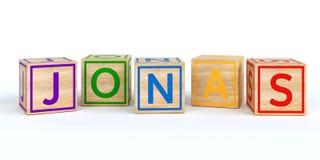 Cubes en bois d'isolement en jouet avec des lettres avec le nom Jonas Photographie stock
