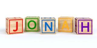 Cubes en bois d'isolement en jouet avec des lettres avec le nom Jonas Image stock