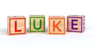 Cubes en bois d'isolement en jouet avec des lettres avec le nom Luc Image libre de droits