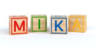 Cubes en bois d'isolement en jouet avec des lettres avec le nom Mika Photos stock