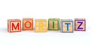 Cubes en bois d'isolement en jouet avec des lettres avec le nom moritz Photos stock