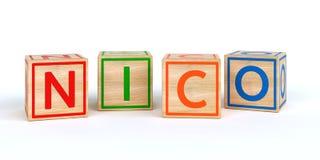 Cubes en bois d'isolement en jouet avec des lettres avec le nom Nico Images libres de droits
